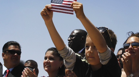 latino_child_holding_flag_in_crowd_2_0