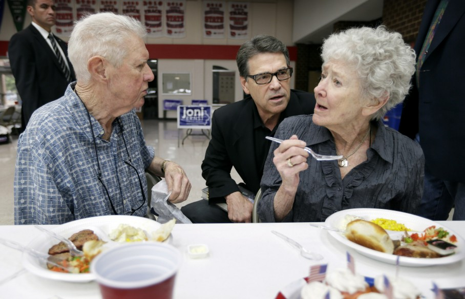 Texas Gov. Rick Perry talks with Dick Dale, left, and his wife Margurite, right, of Algona, Iowa, during a meeting with local party activists, Saturday, July 19, 2014, in Algona, Iowa.