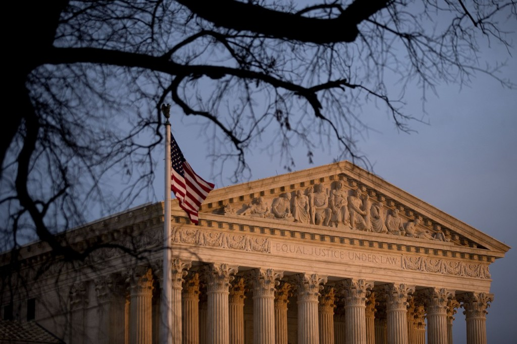 The U.S. flag flies in front of the Supreme Court building at sunset in Washington, D.C., U.S., on Tuesday, Dec. 9, 2014.