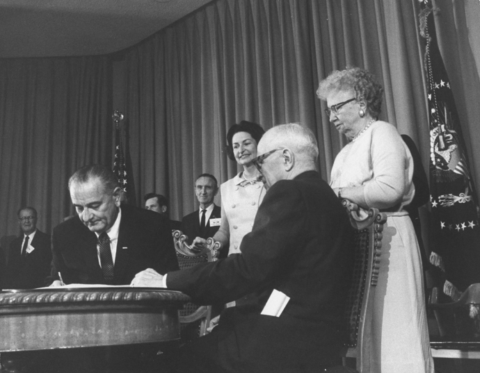 Lady Bird Johnson, former President Harry Truman, and Bess Truman look on as President Lyndon Johnson signs Medicare into law.