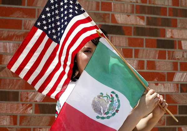 An undocumented immigrant poses for a portrait with the American and Mexican flags Thursday May 16, 2013 in Odessa, Texas. Undocumented immigrants in Texas face a number of legal challenges, including the threat of arrest and deportation. (AP Photo/Odessa American, Edyta Blaszczyk) ** Usable by LA and DC Only **