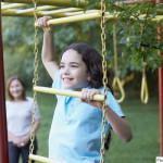 Young girl outdoors at playground climbing with senior woman in background smiling