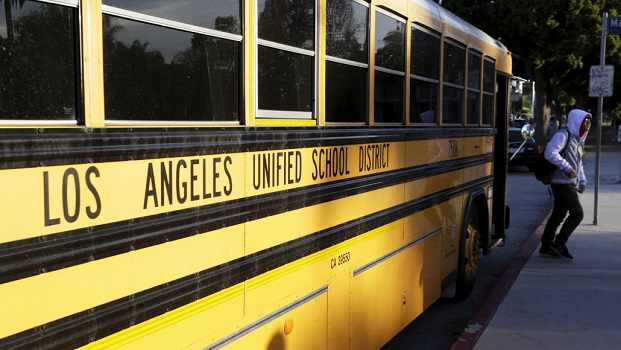 A student exits a bus as he arrives at Venice High School in Los Angeles, California