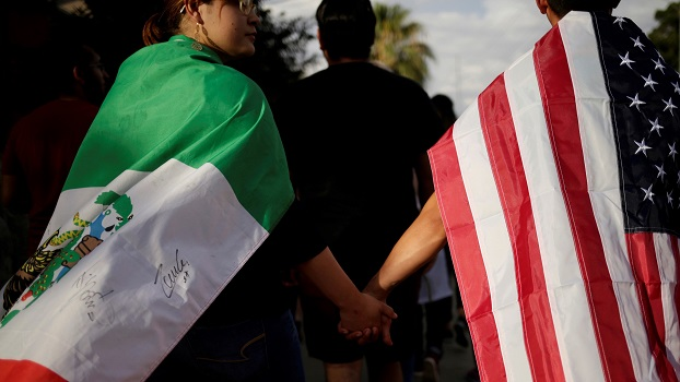 People with the Mexican flag and the U.S. flag take part in a rally against hate a day after a mass shooting at a Walmart store, in El Paso